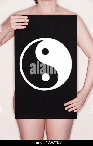 Donna che mantiene una lavagna con un Yin Yang simbolo disegnato su di esso in gesso. Concetto di immagine Foto Stock