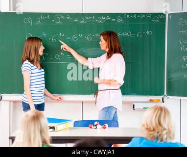 Schoolgirl con insegnante alla lavagna con la formula Foto Stock