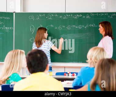 La scolaretta formula di scrittura alla lavagna Foto Stock