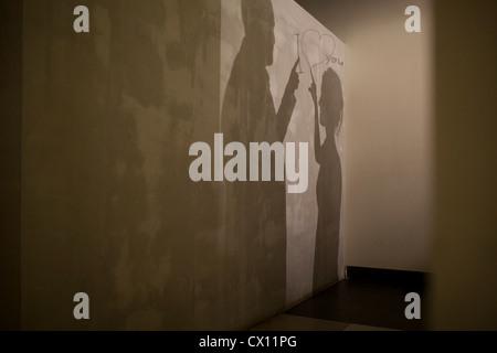 Le ombre del giovane e il messaggio di amore sulla parete Foto Stock