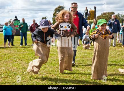I bambini nel sacco di patate gara all'annuale Spaventapasseri Festival tenutosi a Summerside, Prince Edward Island, Canada. Foto Stock