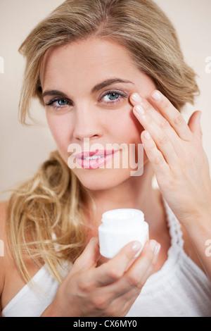 Una giovane donna bionda di applicare una crema idratante per il viso da vicino Foto Stock