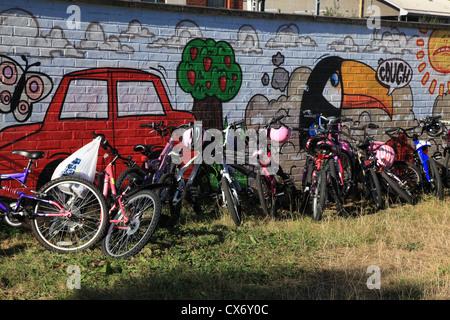 Biciclette in un parco giochi scuola appoggiata contro un murale dipinto su una parete. Foto Stock