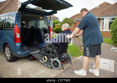 Caregiver maschio figlio spingendo un disabile uomo anziano in una sedia a rotelle su un costruito in rampa in un Foto Stock