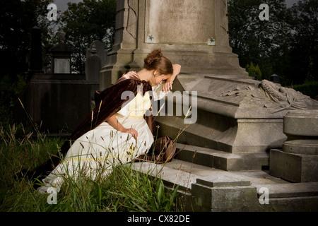Giovane donna in abito vittoriano lutto su una tomba Foto Stock