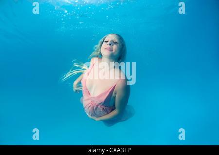 Incinta donna giovane con grandi capelli in posa di un subacqueo in piscina Foto Stock