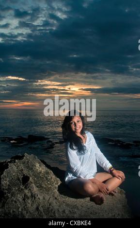 Giovane ragazza seduta sulle rocce dalla spiaggia di Bali, Indonesia.