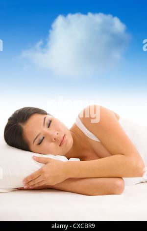 Giovane ragazza asiatica di dormire su un cuscino con la nuvola bianca sulla sua parte superiore Foto Stock