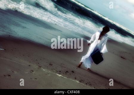 Una ragazza in un abito bianco al mare con una valigia Foto Stock