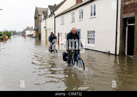 I ciclisti in South Street Bridport dove le case e le imprese sono stati inondati dopo heavy rain. Bridport Dorset Foto Stock