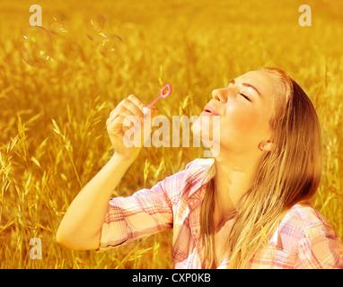 Immagine della carina ragazza bionda soffiando bolle di sapone sul campo di grano, felice adolescente divertirsi Foto Stock
