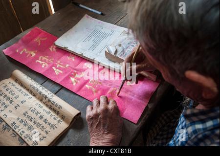 Anziani uomo cinese seduti ad una scrivania, minoranza etnica, pratica antica la calligrafia cinese, Thailandia Foto Stock