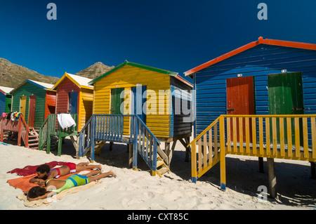 La gente a prendere il sole sulla spiaggia di fronte della pittoresca spiaggia di capanne, Muizenberg, Western Cape, Foto Stock