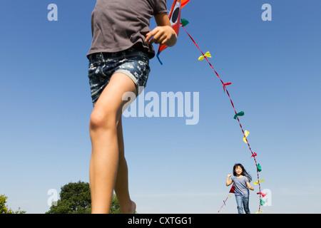 Bambini che giocano con aquiloni all'aperto Foto Stock
