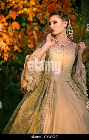 Una bruna giovane donna vestita di un elegante abito vintage in piedi di fronte a colori d'autunno alberi