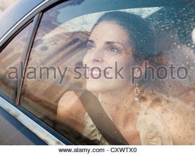 Donna sorridente a guardare fuori dalla finestra per auto Foto Stock