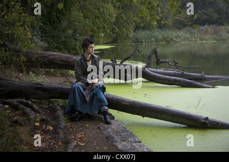Giovane donna si siede da solo lungo il lago in Prospect Park di Brooklyn, New York. Foto Stock