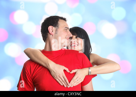 Coppia giovane abbracciando e formando una a forma di cuore gesti con le mani Foto Stock