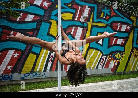 Un ballerino esegue la posa su un palo esterno accanto a un grafitti urbano. Foto Stock