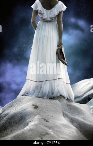 Una ragazza in un abito bianco con la polka dots è in piedi sulle rocce, tenendo le sue scarpe nelle sue mani