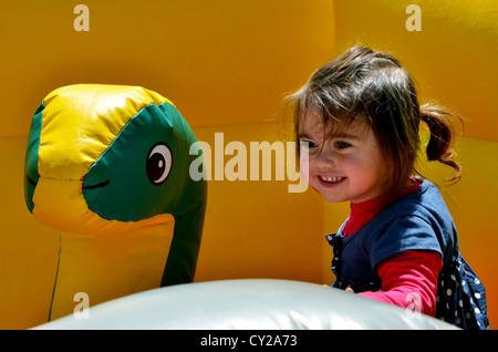 Bambino felice ragazzina salta su di un bambini bouncy castello gonfiabile parco giochi del ponticello. Foto Stock