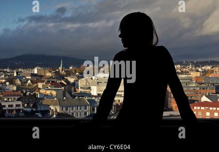Una giovane donna guarda fuori da una finestra su una città europea (Oslo, Norvegia) Foto Stock