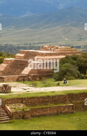 Uomo ispanico si siede vicino a piramide a monte alban sito archeologico, oaxaca, Messico Foto Stock