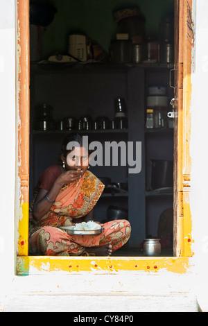 Giovane donna indiana seduto in casa sua porta a mangiare riso. Andhra Pradesh, India