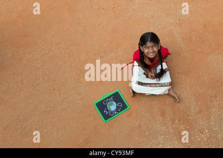 Villaggio indiano ragazza con un mondo scritto su una lavagna in un territorio rurale villaggio indiano. Andhra Pradesh, India. Copia dello spazio.