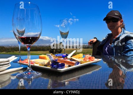 Cape Town, Sud Africa. Un turista a una degustazione di vino in una città del capo azienda vinicola con Table Mountain in background Foto Stock