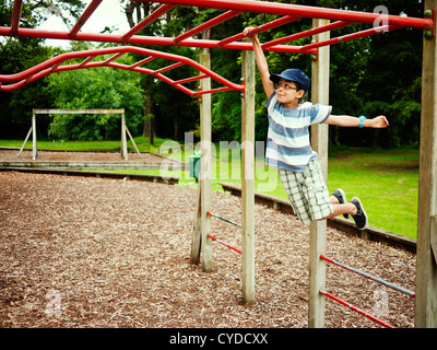 Bambini swing sulla Monkey bar nel parco giochi avventura, Nuova Zelanda. Foto Stock
