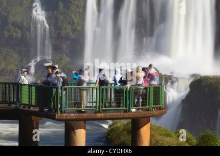 I turisti sul marciapiede a cascate Iguacu, Iguacu National Park, Parana, Brasile Foto Stock