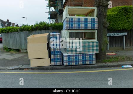 Volare il ribaltamento di vecchi letti e materassi sul marciapiede in strada residenziale a Brent Cross Golders Foto Stock