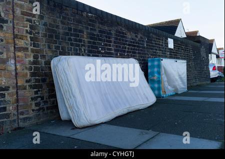 Volare il ribaltamento di vecchi letti e materassi sul marciapiede in strada residenziale di Brent Cross Golders Foto Stock