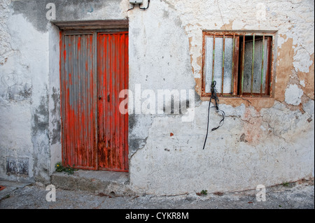 Red porta di metallo e hanno impedito il window set contro un peeling parete dipinta, Andalusia, Spagna Foto Stock