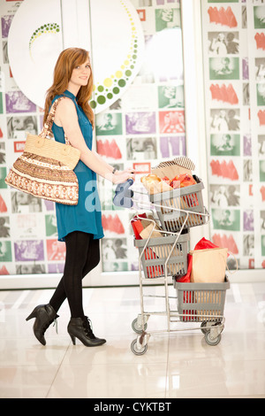 Donna spingendo il carrello di shopping nel centro commerciale Foto Stock