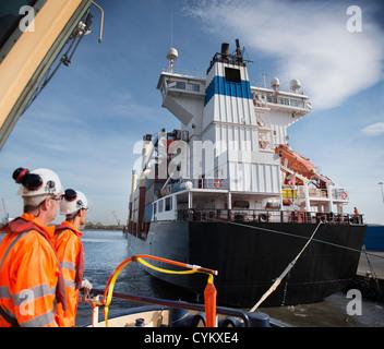 Lavoratori sul rimorchiatore affacciato sulla nave Foto Stock