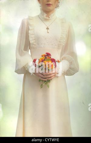 Una ragazza in un abito vittoriano su un prato con un mazzo di fiori Foto Stock