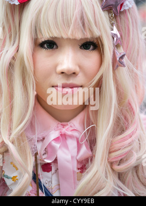 Giovane donna giapponese in kawaii lolita alternative fashion costume con capelli biondi e abito rosa Foto Stock