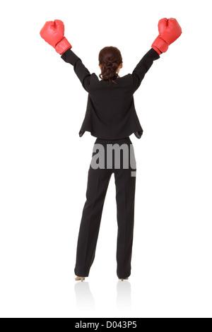Vincitore, donna d'affari di successo di alzare la mano con il rosso guantoni da pugilato, vista posteriore a piena Foto Stock