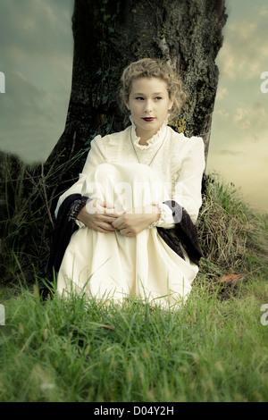 Una ragazza in un abito vittoriano è seduto sotto un albero Foto Stock
