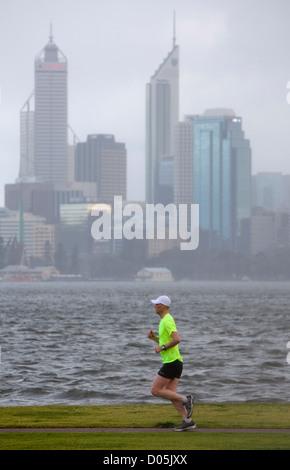 Un uomo jogging sotto la pioggia con un fiume e la città in background. Foto Stock