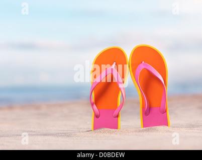 In prossimità di una coppia di colorato arancione flip flop nella sabbia in spiaggia sotto il cielo blu sullo sfondo Foto Stock