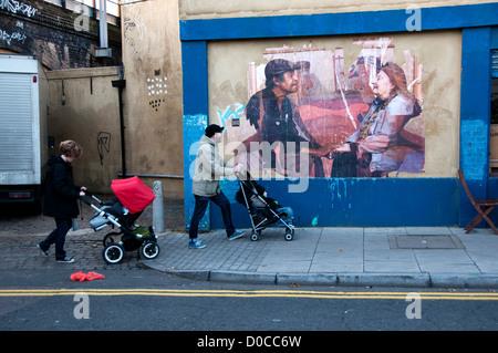 Hackney 18 novembre 2012. Angolo della Andrews Road e Mare Street. Foto di peeling sulla parete cafe e due persone Foto Stock