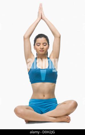 Giovane donna a praticare yoga contro uno sfondo bianco Foto Stock