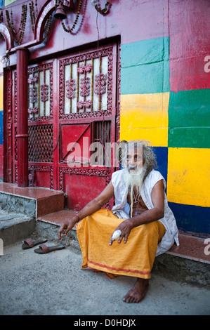 Santo uomo seduto al di fuori del santuario di Chandni Chowk, Vecchia Delhi, India Foto Stock