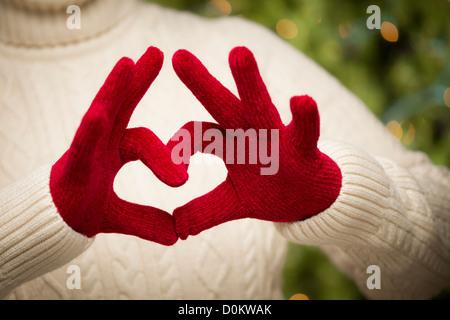 Donna in felpa con Rosso stagionale muffole tenendo fuori un cuore segno con le mani. Foto Stock