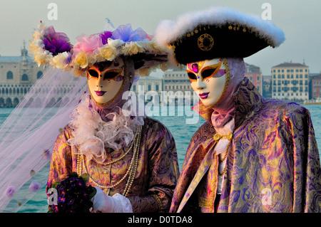 Mascherare i partecipanti si affacciano sul Canal Grande di fronte alla chiesa di San Giorgio Maggiore a Venezia Foto Stock