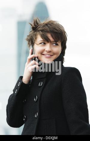 Donna sul cellulare nella giornata di vento Foto Stock
