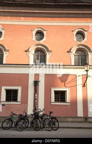 Lunga ombra di mattina presto sulla lampada ornata al di fuori del vecchio edificio rosa con le biciclette parcheggiate Foto Stock